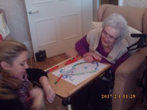 resident and student chatting and colouring