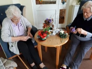 two lady residents making Christmas flower arrangements