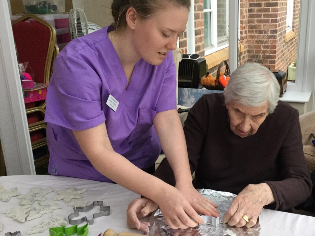 resident crafting with the help of a carer