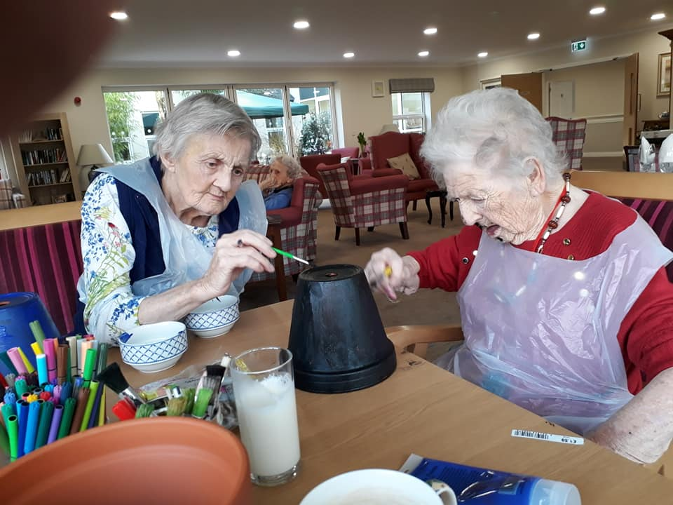 Two lady residents painting flower pots for winter craft