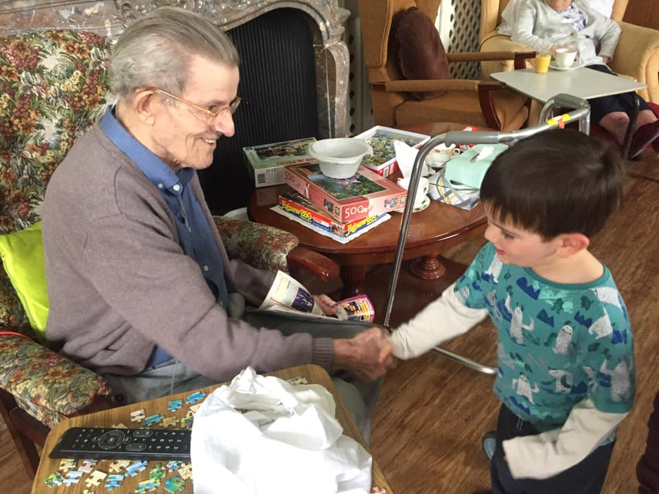 Gentleman resident and boy shaking hands after puzzling