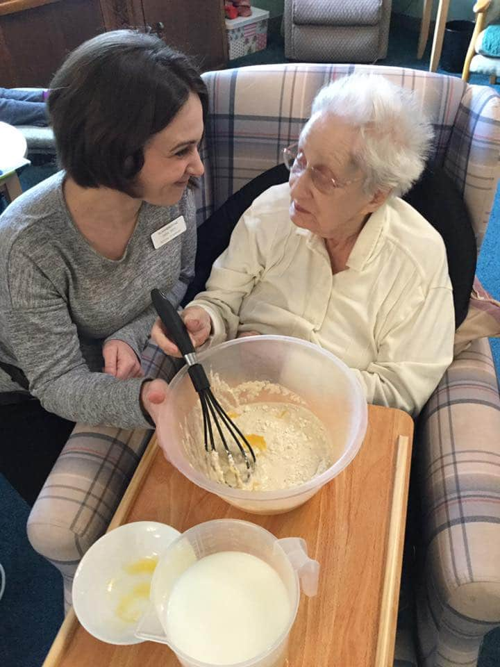 Emma and lady resident making pancakes - activities