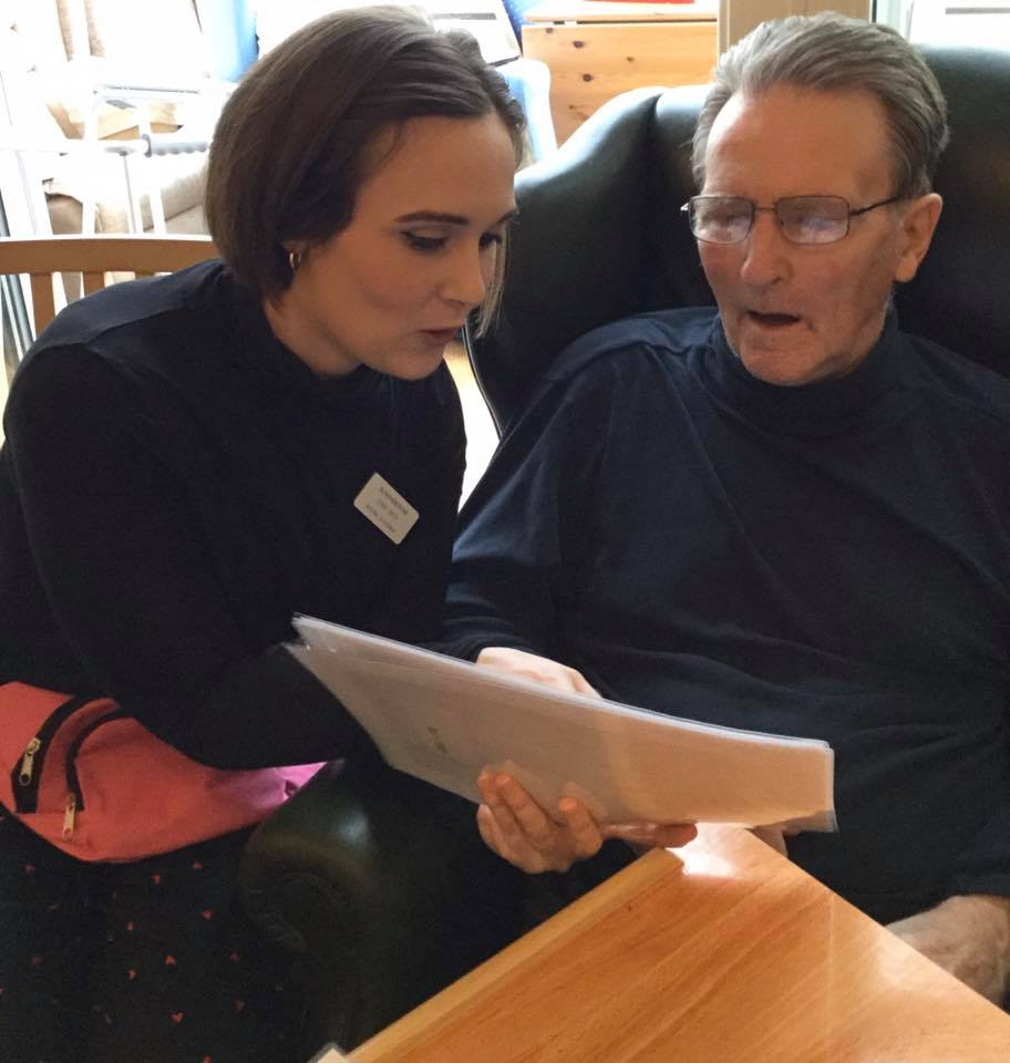 Emma reading with a gentleman resident