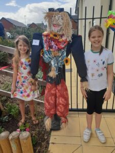 Two children proudly with their scarecrow