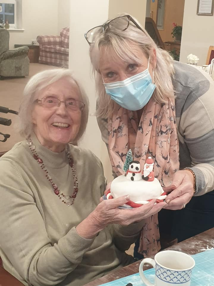 Mel and Resident icing a cake