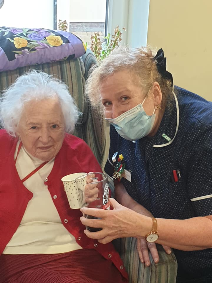 Lady resident and carer have Christmas tipple