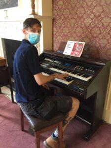 Chris at Abberton demonstrating his piano skills to residents