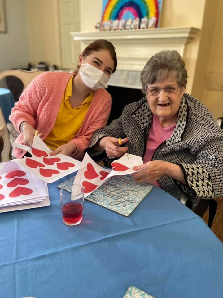 valentines day crafting - Victoria and lady resident cutting hearts