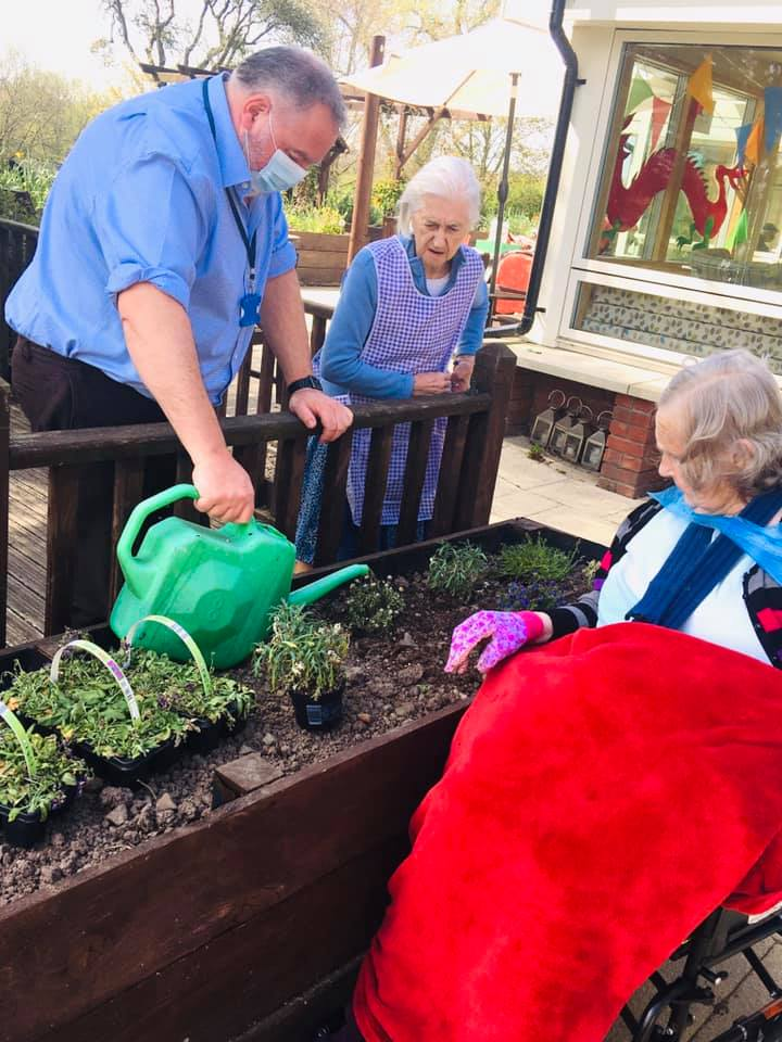 residents and roddy potting up on the patio raised beds