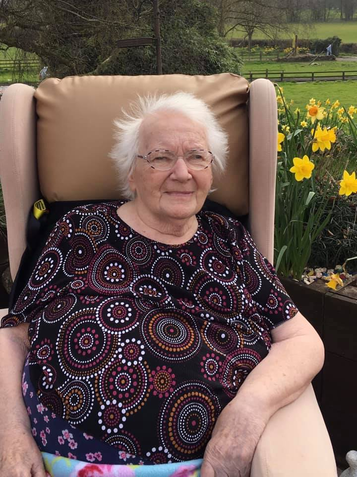 lady resident outside on the patio with daffs