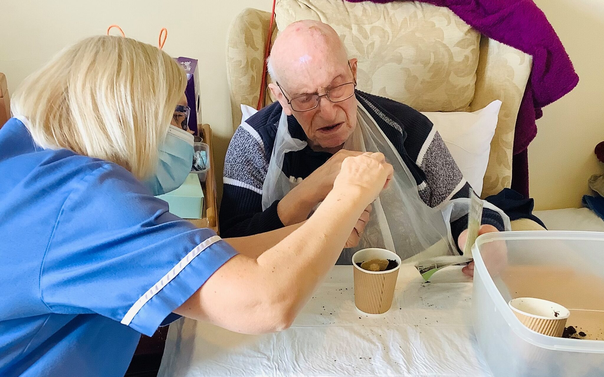 Maytime activities Abberton - gentleman resident and carer planting seeds