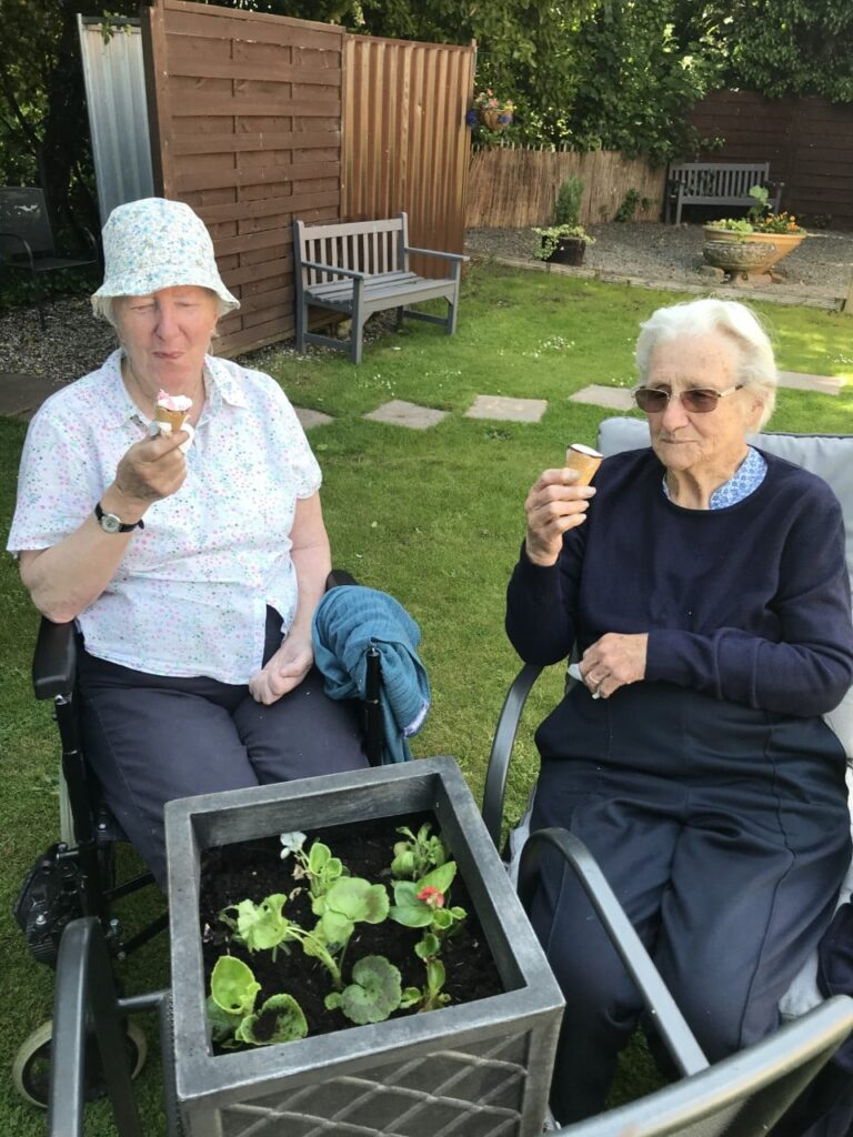 2 lady residents eating ice creams and gardening together