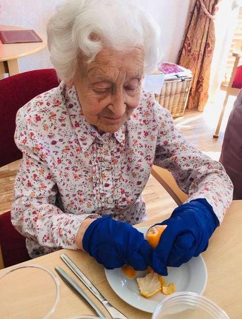 lady making fruit kebabs- peeling an orange