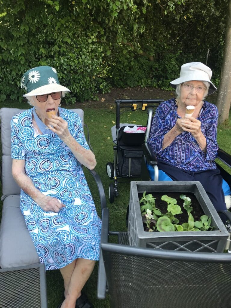 2 lady residents gardening and eating ice cream (wearing hats)