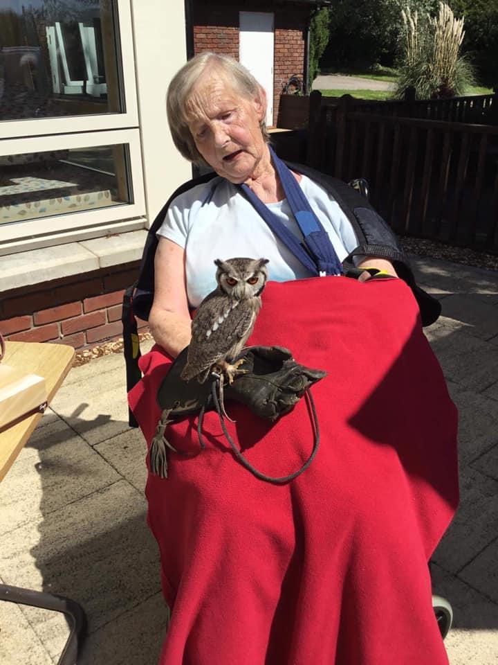 lady resident holding owl over red blanket - making new memories